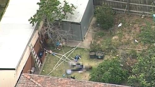 Man arrested over body in backyard west of Melbourne