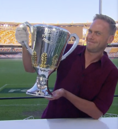 Tim Davies gets his hands on the AFL Premiership Cup