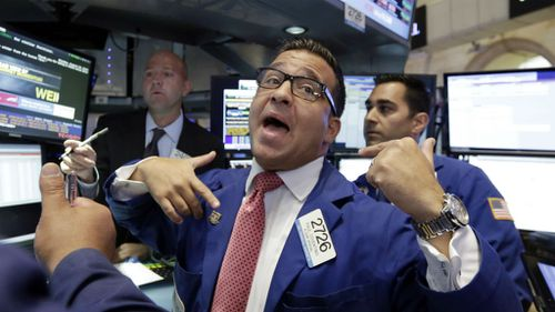 Specialist Paul Cosentino, centre, works at his post on the floor of the New York Stock Exchange.