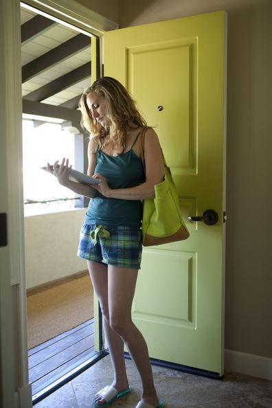 Woman looking at tablet device in doorway