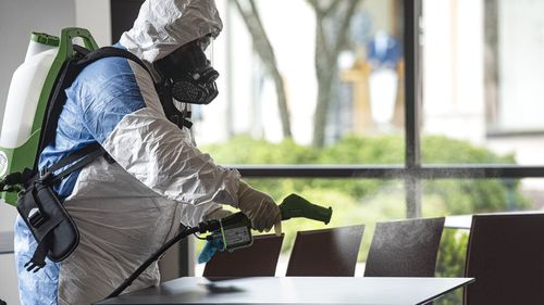 Service technician Hazel Maldonado of Guardian Touchless Solutions wears a protective suit as he uses an electrostatic gun to clean Villaggio del Vino in Tyler, Texas.