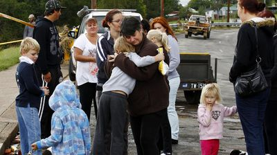 Dungog residents comforting each other after heavy floods devastated their town. (AAP)