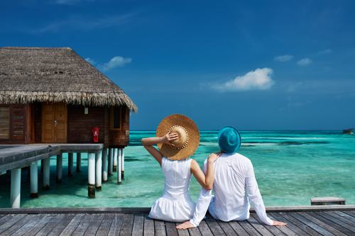 Couple on a tropical holiday with overwater bungalow / bure | Honeymoon in Maldives