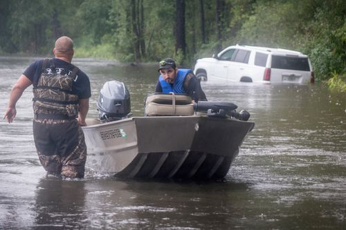 A Dillon County rescue crew boat works in a flooded area near a stuck car in Latta, South Carolina.