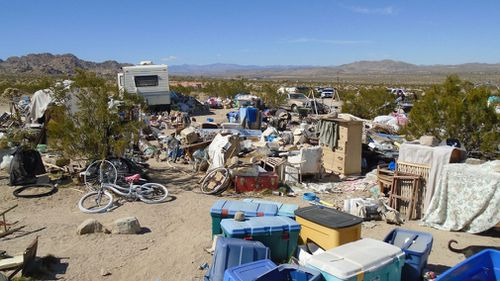 A makeshift kitchen was littered with empty bottles with cans of corn, peas and soup stacked on wooden shelves. Several holes on the property were filled with faeces, officials said. (Morongo Basin Sheriff Station)