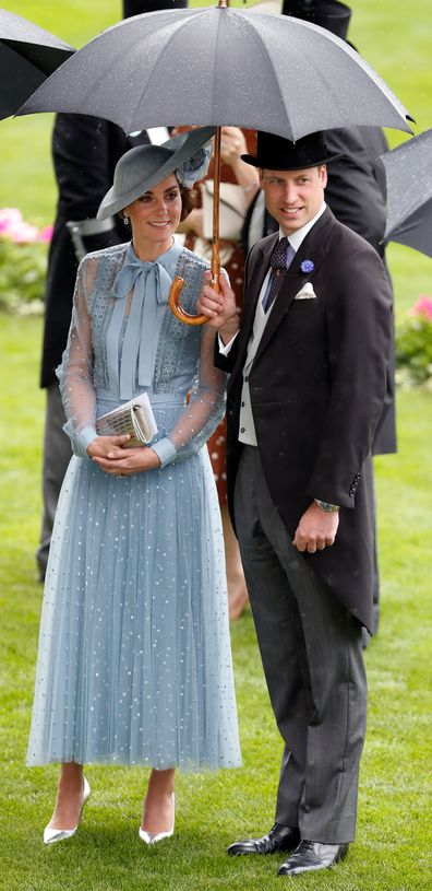 Prince William and Kate Middleton shelter under an umbrella at Royal Ascot