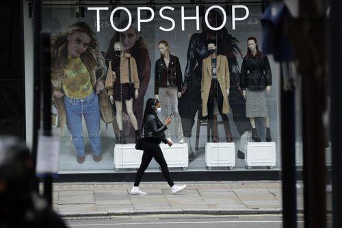 زنی با ماسک صورت در حالی که دومین قفل ویروس کرونا در انگلستان ، در لندن ، با استفاده از ماسک صورت در پنجره شاخه موقتاً بسته شده از زنجیره لباس زنانه Topshop ، از کنار مانکن هایی عبور می کند.