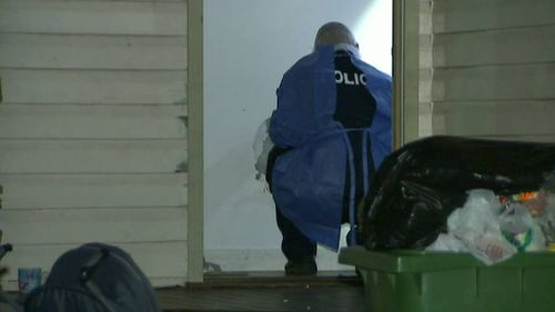 An officer examines a doorway to the home. (9NEWS)