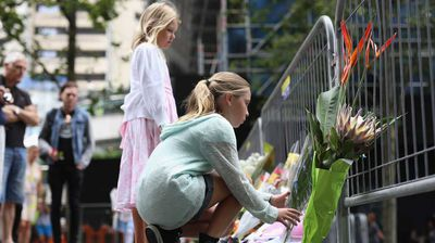Two young girls place their tributes in a newly designated memorial area set up due to a growing number of flowers and tributes left at the site.