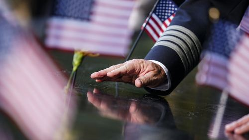 A person touches an inscribed name at the National September 11 Memorial and Museum ahead of the 20th anniversary of the 9/11 terrorist attacks in New York City.