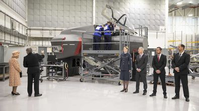 The Queen watches air crew at work on a training model F-35B Lightning II fighter.