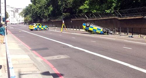 A police car flipped in a pursuit near Buckingham Palace yesterday. Image: AAP