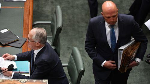 Peter Dutton walks behind Malcolm Turnbull at Question Time yesterday.