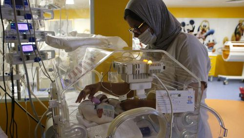A Moroccan nurse takes care of one of the nine babies protected in an incubator at the maternity ward of the private clinic of Ain Borja in Casablanca, Morocco.