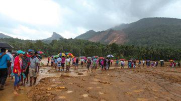 Landslide survivors walk through the mud after a landslide in the Kegalle district of Sri Lanka. (AFP)