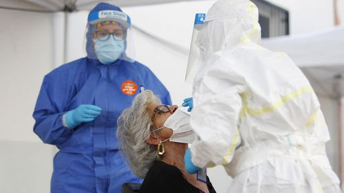 Health workers in personal protective equipment (PPE) suits collect a swab sample from people during the express COVID-19 testing in Alfacar, Granada, Spain.