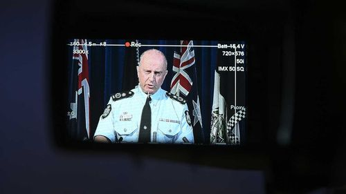 Acting AFP Commissioner Neil Gaughan is seen through a view finder as he speaks to the media.