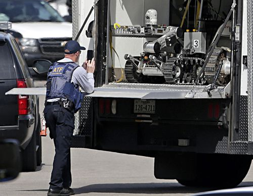 Hi-tech bomb disposal robots have been brought in to help the search for weapons inside the bomber's home. (AAP)