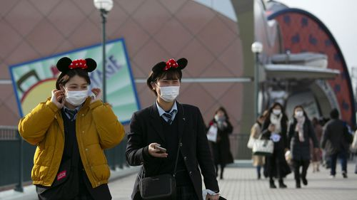 Two visitors with masks and Minnie Mouse ear headbands leave Tokyo Disneyland in Urayasu, near Tokyo, Friday, Feb. 28, 2020