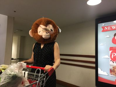 Mum grocery shopping wearing gorilla head