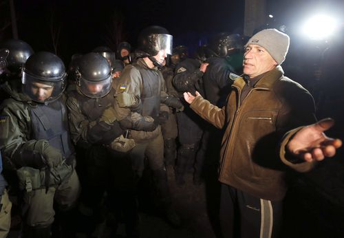Protesters, who planned to stop buses carrying passengers evacuated from the Chinese city of Wuhan, speak to Ukrainian riot police.