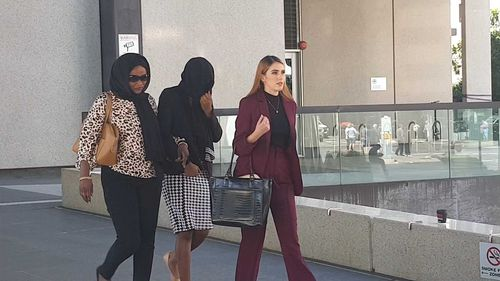 Diana Lasu leaves Brisbane Magistrates Court covering her face and linking arms with her mother.