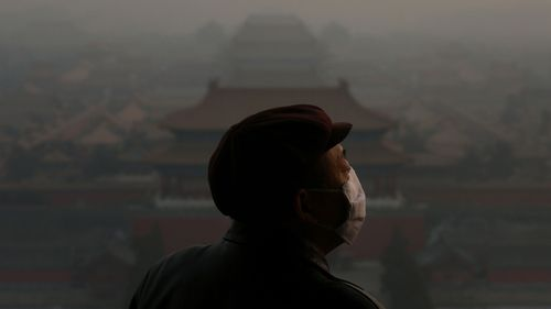 Heavy smog shrouded the Forbidden City in Beijing, China as a tourist looks on.