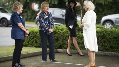 Camilla, Duchess of Cornwall speaks to a worker during a visit with Prince Charles, Prince of Wales to the Turnbull & Asser shirt factory on July 9, 2020 in Gloucester, United Kingdom