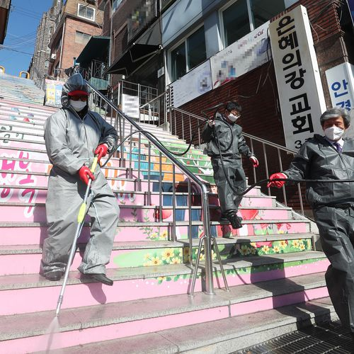 Hygiene officials disinfect an area around temporarily closed River of Grace Community Church in Seongnam, South Korea.