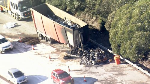 A truck sits burned out on the M1.