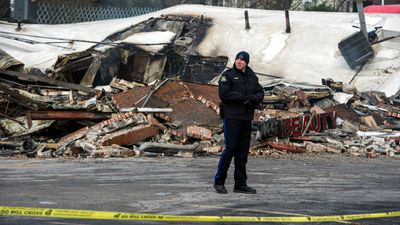 A policeman surveys the damage after last night's riots in Ferguson, Missouri. Violence erupted when a grand jury voted not to indict Darren Wilson over the shooting death of Michael Brown. (AAP)