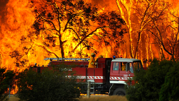 A Country Fire Authority (CFA) fire truck is pictured in front of flames while fighting a bushfire at the Bunyip State Forest near the township of Tonimbuk, Saturday, Feb. 7,