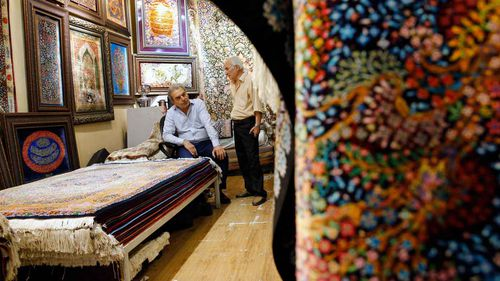Iranian men chat inside their carpet shop at Tehran's old Bazaar. (AAP)
