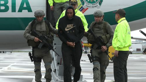 Former Colombian soccer player Jhon Viafara (C) walks scorted by members of Colombian Police upon his arrival to Catam military airport in Bogota, Colombia