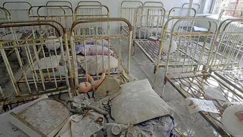 Children's toys and gas masks, covered by radioactive dust, are seen on beds in an abandoned kindergarten in the ghost town of Pripyat.