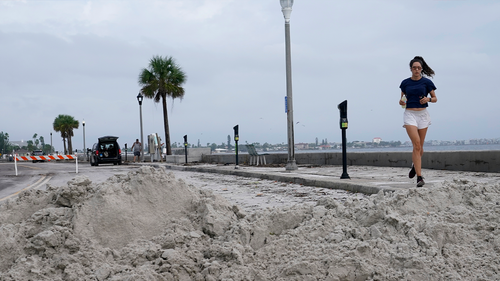 A woman jogs past a pile of sand which washed ashore in the in the Passe-A-Grille neighborhood of St. Pete Beach, Florida. in the aftermath of Tropical Storm Eta, Thursday, November 12, 2020. (AP Photo/Lynne Sladky)