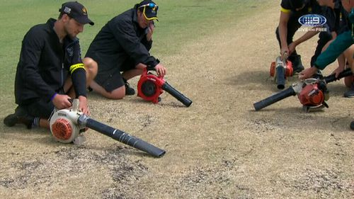 Ground staff used blower vacuums in a bid to dry the pitch.