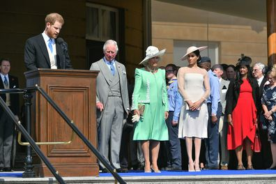 The Prince of Wales, the Duchess of Cornwall and the Duchess of Sussex, listen as the Duke of Sussex speaks during a garden party at Buckingham Palace in London.