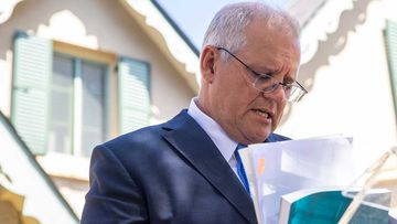Prime Minister Scott Morrison looks through documents as he delivers the Royal Commission Report into Aged Care.