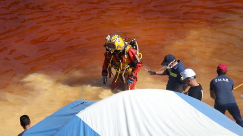 A police diver searches for a suitcase with a fifth body at the Red Lake in Mitsero village, Cyprus.