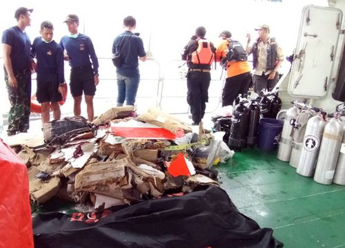 Rescuers collect bodies of plane crash victims in a bag on the Indonesia Search And Rescue boat.