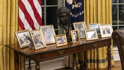 The Oval Office of the White House is newly redecorated for the first day of President Joe Biden's administration, Wednesday, Jan. 20, 2021, in Washington, including a table with family photos.