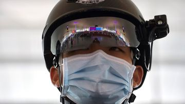 A police officer wearing a face mask to protect against the spread of new coronavirus stands guard at Wuhan Tianhe International Airport in Wuhan in central China's Hubei Province