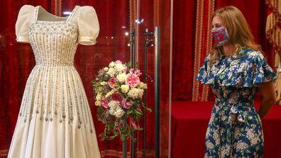 Princess Beatrice poses alongside her wedding dress as it goes on display at Windsor Castle on September 23, 2020 in Windsor, England