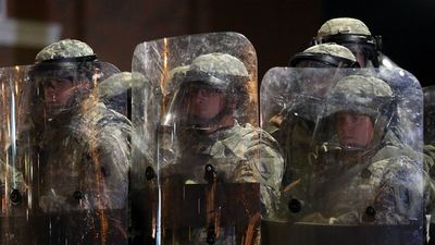 Soldiers from the Missouri National Guard stand guard outside the Ferguson police station. (Getty Images)