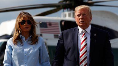 President Donald Trump, with first lady Melania Trump, walks towards the media.