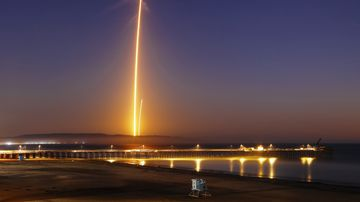 Two streaks in this long exposure photo show a SpaceX Falcon 9 rocket lifting off, left, from Vandenberg Air Force Base, as seen from Pismo Beach