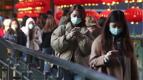 People wear face masks and walk at a shopping mall in Taipei, Taiwan.