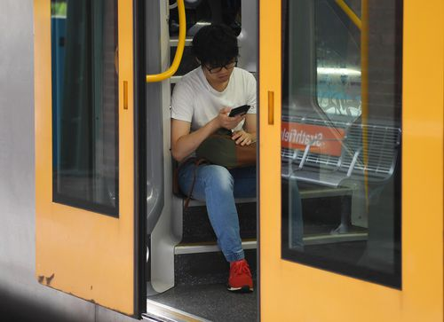 A commuter sits on the steps of a Sydney Trains carriage during rush hour at Strathfield train station. (AAP)