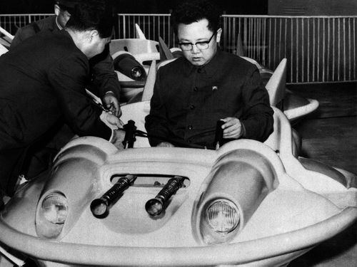 In this October 2, 1977 photo from North Korea's official Korean Central News Agency, distributed by Korea News Service, leader Kim Jon Il has a test drive of a play equipment combat plane in Taesong amusement park. (AP)